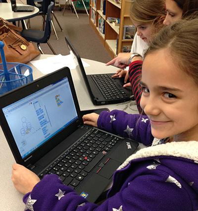 photo of grinning girl using laptop